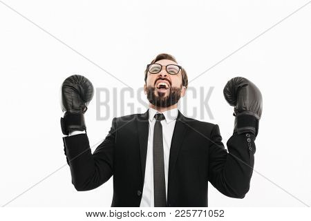 Portrait of emotional businessman in black suit and eyeglasses rejoicing his win in boxing gloves, isolated over white background