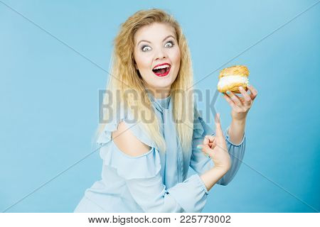 Sweet Food And Happiness Concept. Funny Joyful Blonde Woman Holding Yummy Choux Puff Cake With Whipp