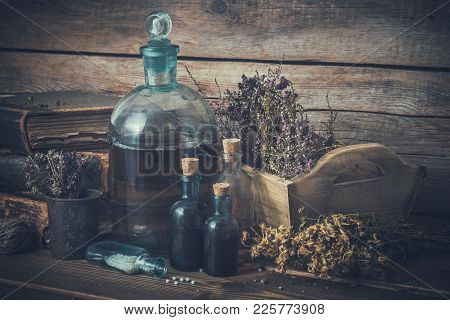 Tincture Bottles, Vial Of Homeopathy Globules, Old Books, Dry Healthy Herbs And Curative Drugs. Herb