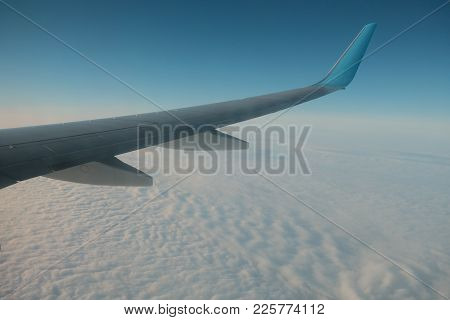View Of Jet Airplane Wing Flying Over Cloud Cover In Blue Sky In Daytime.
