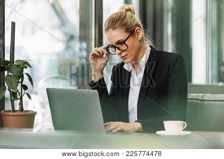 Image of young concentrated blonde business woman sitting indoors in cafe drinking coffee using laptop computer. Looking aside.
