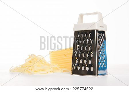 Grated Cheddar Cheese And Metal Grater Isolated On White Background With Copy Space, Close-up.