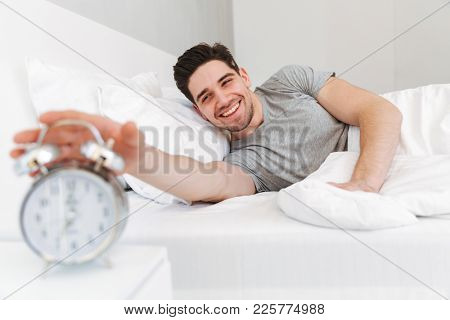 Image of young handsome cheerful man lies in bed indoors wake up turn off the alarm clock.