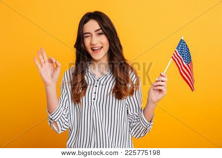 Portrait of a pretty young girl winking and showing ok gesture while holding american flag isolated over yellow background