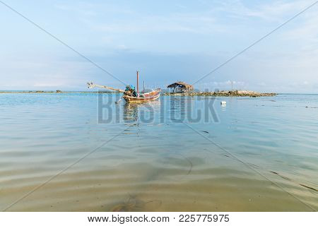 Asian Idyllic Picturesque Coastal Scene With Traditional Long Tail Fishing Boat Floating On Calm Tur