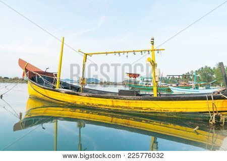 Classical Curving Lines Of Bright Yellow Traditional  Wooden Boat Reflected In Calm Water Moored On