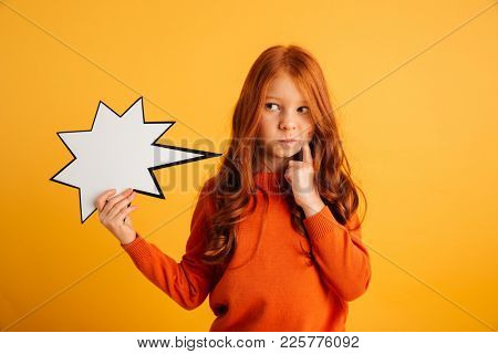 Image of thinking little redhead girl with freckles standing isolated over yellow background holding speech bubble. Looking aside.