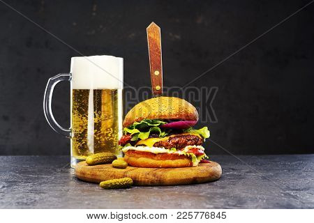 Delicious Beef Burger With A Glass Of Beer On The Board With Cheese, Vegetables And Lettuce, Hand Ma