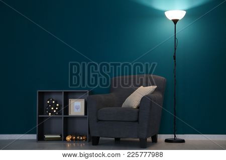 Elegant living room interior with comfortable armchair and shelving unit near wall