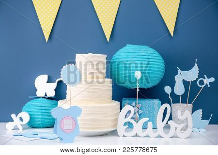 Yummy cake, decorations and Thank you card for baby shower party on table near color wall