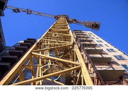 Modern Apartment Building With Tower Crane On Blue Sky Background