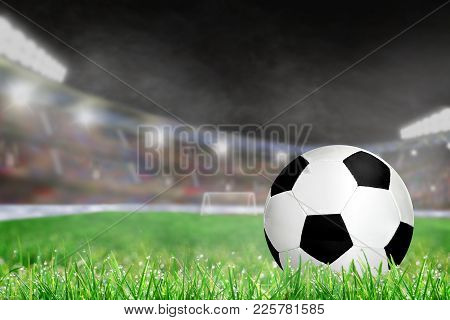 Soccer Ball On Field Grass In Brightly Lit Outdoor Stadium With Focus On Foreground And Deliberate S