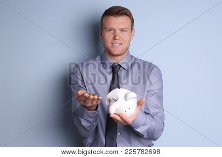 Young man with broken piggy bank and coins on color background