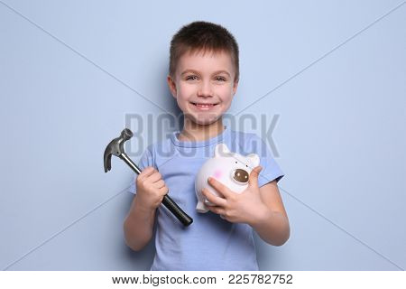 Cute boy holding hammer and piggy bank on color background