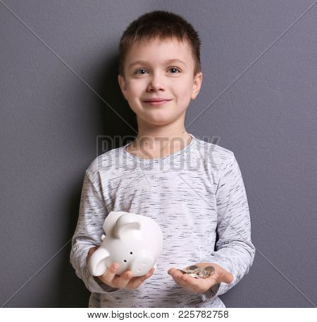 Cute boy holding broken piggy bank and coins on grey background