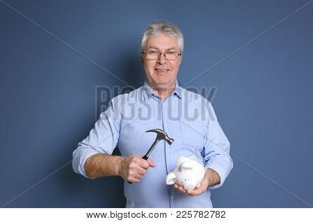 Mature man holding hammer over piggy bank on color background