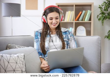 Woman listening to audiobook through headphones at home