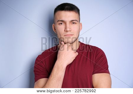 Young man with dyed eyebrows on light background