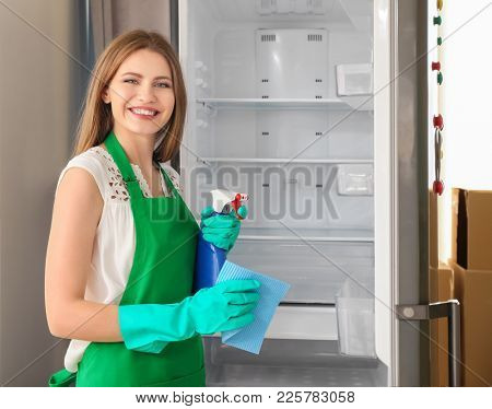 Woman cleaning empty refrigerator in kitchen