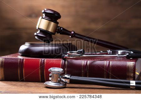 Close-up Of Judge Gavel And Soundboard On Law Book With Stethoscope Over The Wooden Desk