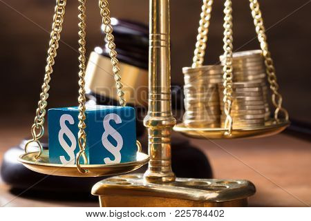 Close-up Of Blue Paragraph Block Balancing With Coins Stack On The Golden Scale Of Justice