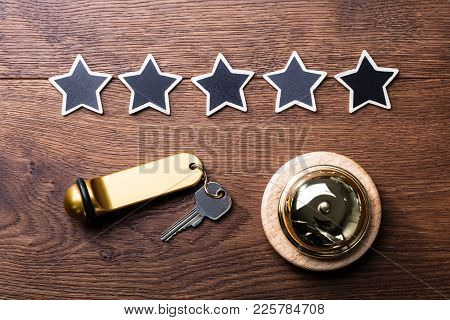 High Angle View Of Black Five Stars, Service Bell And Hotel Key On Wooden Desk