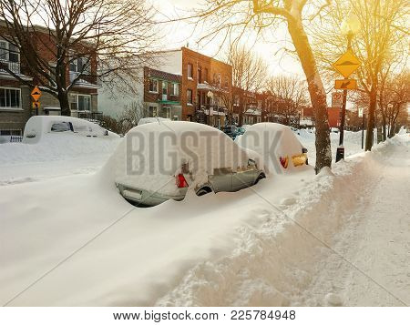 Cars Covered With Snow On Winter Street In Sunset. Montreal, Quebec, Canada.