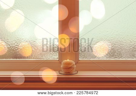 Frosted Winter Window And A Cozy Burning Candle In Golden Light.
