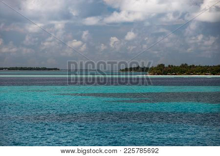 Islands With Numerous Green Vegetation Bushes On Small Islands Atolls Among The Ocean, Maldives.