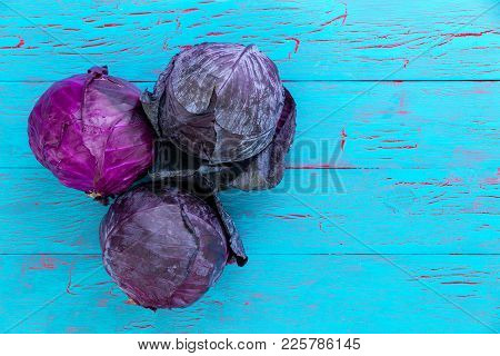Three Healthy Fresh Heads Of Red Or Purple Cabbage, Also Known As Red Kraut, Over A Blue Crackle Pai