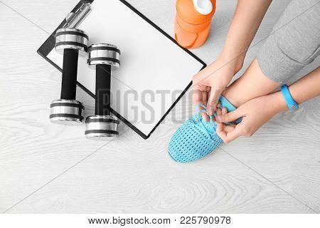 Young woman tying shoelaces on floor, flat lay. Ready for gym workout