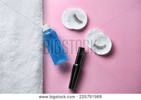 Mascara, makeup remover and cotton pads with false eyelashes on color background