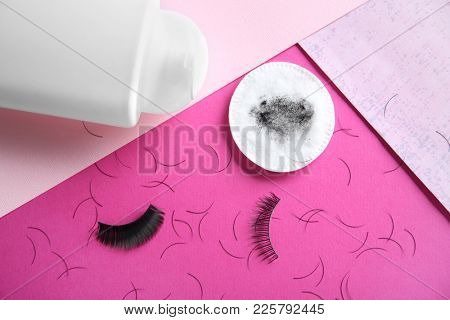 Makeup remover, cotton pad and false eyelashes on color background