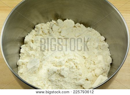 Close Up Of White Cookie Or Cake Dry Mix In Stainless Steel Mixing Bowl As First Step In Making Batt