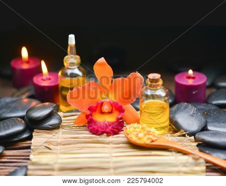 Spa setting with orange orchid, set of candle, black stones,salt in spoon,oil on mat
