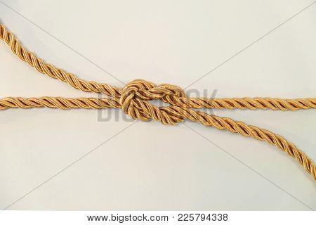 Reef Knot Or Square Knot By Golden Color Rope On White Background
