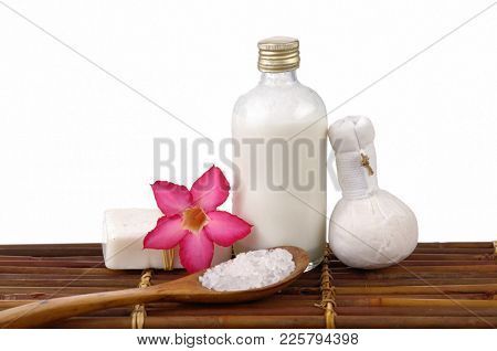 Spa setting with pink rose ,salt in wooden bowl , oil, soap, ball on mat