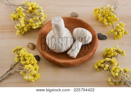 spa setting with yellow helichrysum flowers, herbal ball in wooden bowl ,stones, on woooden background