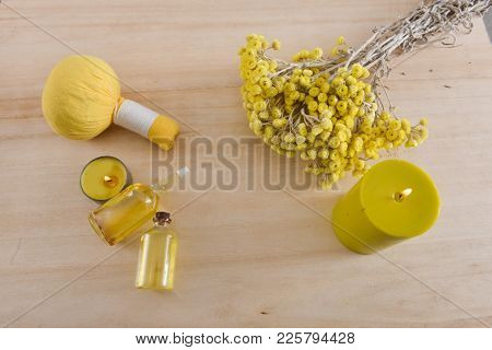 spa setting with yellow helichrysum flowers, herbal ball.candle, bottle oil on wooden background
