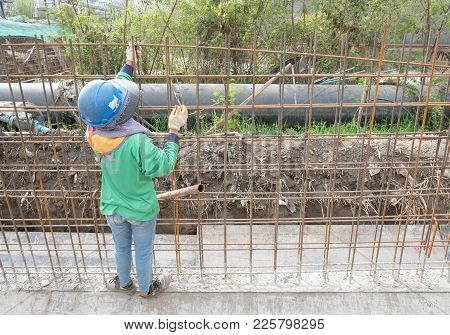 Construction Worker Assembling Steel Bar At Construction Site.