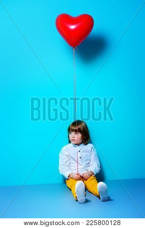 Six-year-old boy holding heart shaped balloon over blue background. Valentine's Day.