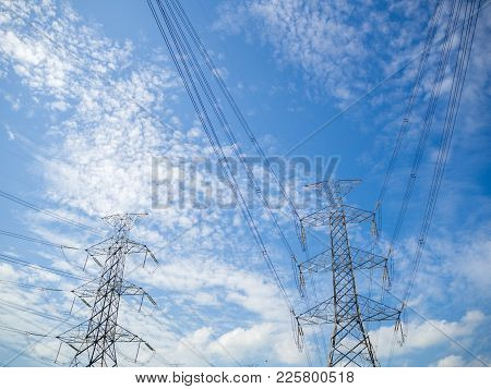 Steel Electricity Pylon On Bright Blue Sky  Background.