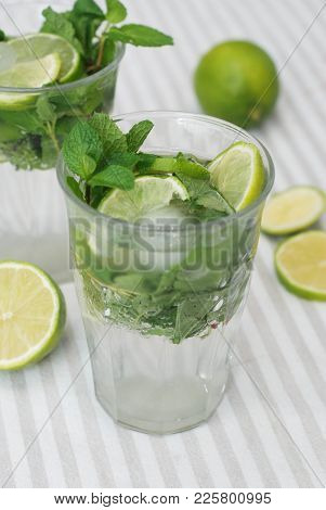 Two Glasses With Mohito And Ice With Lime Citrus Fruits.
