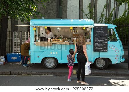 LONDON-ENGLAND, JUNE 10, 2017: Woman and a kids in front of a food truck ready to serves meals in the street.  London's street food dates back centuries and are a part of the londoners culture.