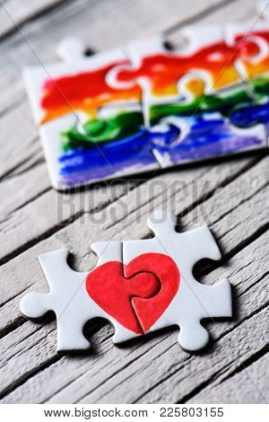 two pieces of a puzzle forming a heart and some other pieces forming a rainbow flag, on a white rustic wooden surface