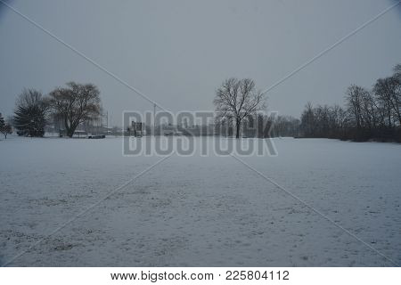 Vast Open Field Covered In Snow In Winter Under A Cloudy Sky