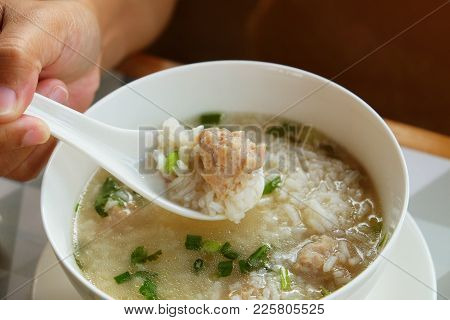 Asian Woman Hand Using Plastic White Spoon To Ladle Porridge Or Rice Congee Mixed With Pork Meat For