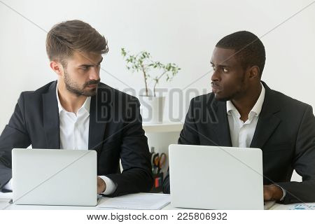 Multiracial Office Rivals Looking At Each Other With Hate Envy Sitting With Laptops, Corporate Compe