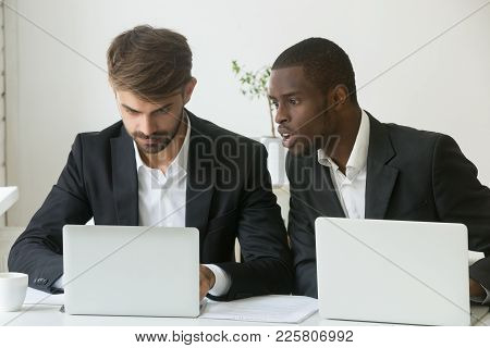 Shocked African Businessman Looking At Laptop Screen Of Caucasian Colleague Stunned By Online News,