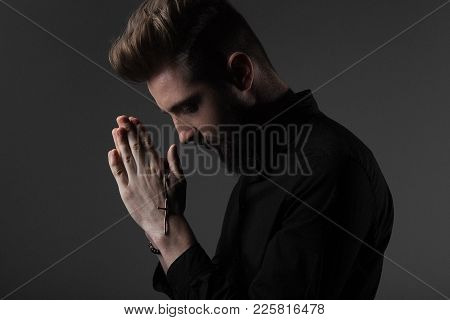 The Priest Clasping His Hands With A Cross At The Head Prays With His Eyes Closed